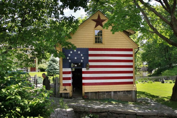 Terry Baron works recently near a garage he restored for a homeowner in Kennebunk. A few days after Baron finished the project in 1998 he returned to discover the owner had painted an early version of an American flag on the side.