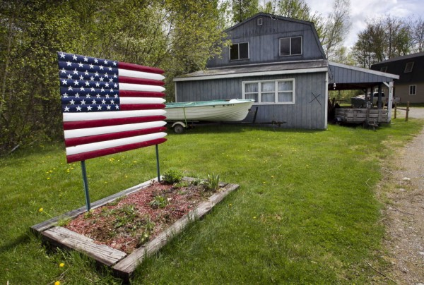 A wooden flag stands in a flower bed at a home on the Airline Road in East Eddington recently.