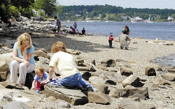 Adults and children relax on the shore at Belfast City Park on a beautiful summer afternoon.