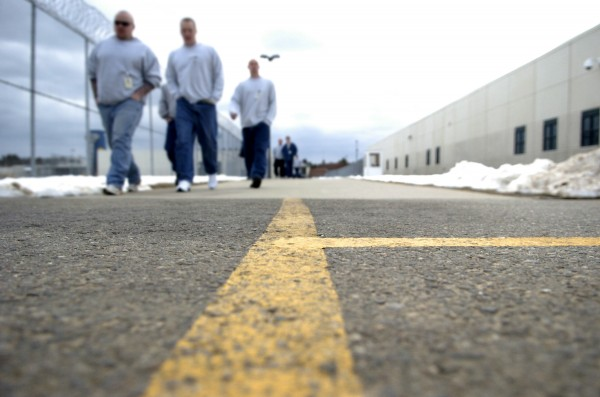 Inmates at Maine State Prison in Warren walk down an outdoor concourse that connects activity areas to cell blocks in April 2007.