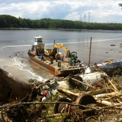 Crews from Maine Coast Marine prepare to use a tugboat and barge to remove several railroad tanker cars that derailed in late May and went into the Penobscot River in Bucksport.