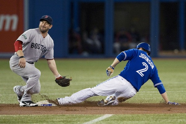 Kelly Johnson of the Toronto Blue Jays slides safely under the tag of Boston Red Sox second baseman Nick Punto as he steals second base during the first inning Sunday, June 3, 2012, in Toronto.