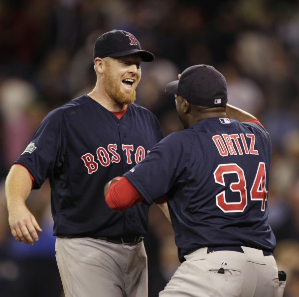 Boston Red Sox starting pitcher Aaron Cook, left, greets David Ortiz after Cook threw a two-hit shutout against the Seattle Mariners in a baseball game, Friday, June 29, 2012, in Seattle. The Red Sox beat the Mariners 5-0.