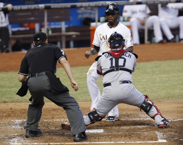 Miami Marlins' Jose Reyes, top right, is tagged out at home plate by Boston Red Sox catcher Kelly Shoppach (10) as Reyes tried to score on a ball hit by Hanley Ramirez in the third inning of an interleague baseball game in Miami, Tuesday, June 12, 2012. Home plate umpire D. J. Reyburn watches.