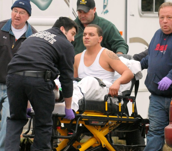 Darren Seidell, 30, a transient originally from Florida, is taken to an ambulance from an Eddington home on Riverside Drive Saturday afternoon after breaking in and then being shot in the foot by the home owner.