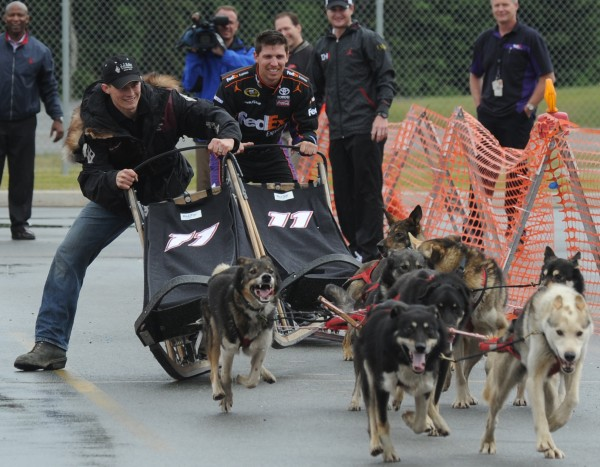 Iditarod and Yukon Quest champion Dallas Seavey slides his dog team past NASCAR driver Denny Hamlin at the FedEx Express Hub in Anchorage, Alaska on Monday, June 25, 2012. Hamlin, who drives the No. 11 FedEx Express Toyota in the NASCAR Sprint Cup Series, visited with some of the 1,350 FedEx team members at the Anchorage hub before learning about the sport of dog mushing before competing in a best-of-3 race in the parking lot. Hamlin won the first race and Seavey won the next two races.