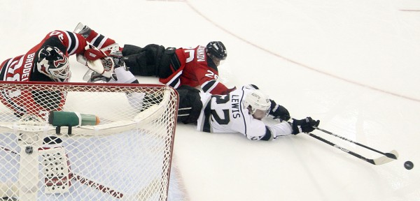 The Los Angeles Kings' Trevor Lewis, right, and the New Jersey Devils' Anton Volchenkov reach for the puck in front of goalie Martin Brodeur in Game 5 of the NHL Stanley Cup Finals on Saturday at the Prudential Center in Newark, New Jersey. The Devils won, 2-1, and trail the series, 3-2.