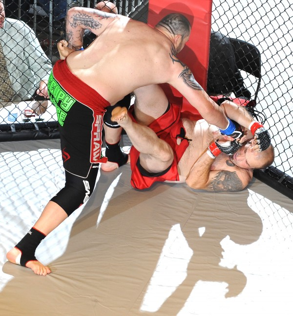 Tim Sylvia (left) delivers punch after punch to Randy Smith as he knocked him out in 12 seconds of the first round of the main event of Fight Night III, a MMA Cagefighting event presented by New England Fights at the Androscoggin Bank Colisee in Lewiston Saturday night.