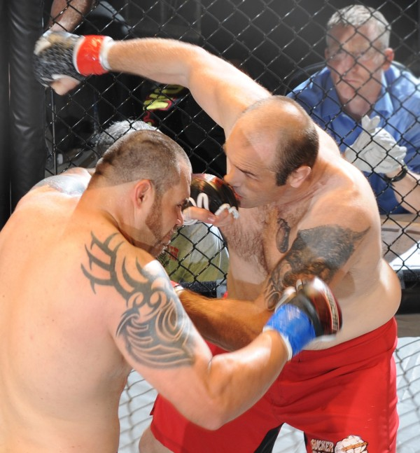 Tim Sylvia (left) connects with a left to Randy Smith during the main event of Fight Night III, a MMA Cagefighting event presented by New England Fights at the Androscoggin Bank Colisee in Lewiston Saturday night. Sylvia knocked Smith out in 12 seconds of the first round.
