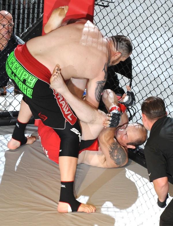 Tim Sylvia (left) connects with a flurry of punches to Randy Smith during the main event of Fight Night III, a MMA Cagefighting event presented by New England Fights at the Androscoggin Bank Colisee in Lewiston Saturday night. Sylvia knocked Smith out in 12 seconds of the first round.
