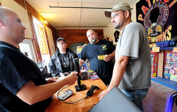 Jay Blais, co-owner of Patriot Fireworks in Monmouth, shows Lewiston residents Jacob Mottram (left to right), 11, his father, Jason Mottram, and Greg Morin how to safely use an Exterminator canister shell firework on Tuesday afternoon. &quotYou should designate a shooter for your Fourth of July parties just like you would a driver,&quot said Blais. &quotAlcohol and fireworks do not mix.&quot