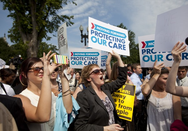 Demonstrators react to the Supreme Court landmark decision on health care, Thursday, June 28, 2012, outside the court in Washington.
