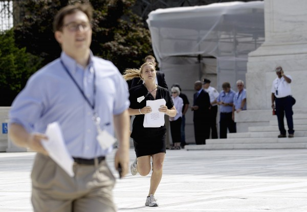 Members of the media run out of the Supreme Court in Washington, Thursday, June 28, 2012, after the court's ruling on President Barack Obama's health care law was announced.