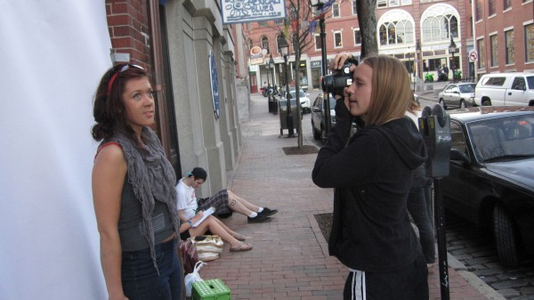 Ellen Sherwood (right), a student at the Salt Institute for Documentary Studies, takes a portrait of a passer-by for an art project in Portland, Maine in March 2012.
