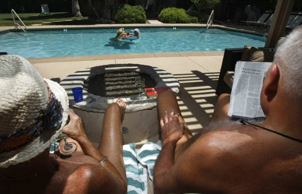 Judy (left) and her husband, Mike, lounge by the pool at the Desert Sun Resort in Palm Springs, California, May 10, 2010. The Maryland couple has been making the resort their vacation destination for the past 7 years. They agree with the owner's recent decision to restrict children from the nudist resort.