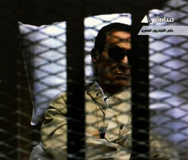 A television screen show former Egyptian President Hosni Mubarak being broughy into a security cage on his medical stretcher shortly before the judge sentenced him to life in prison in Cairo, Egypt, Saturday, June 2, 2012.