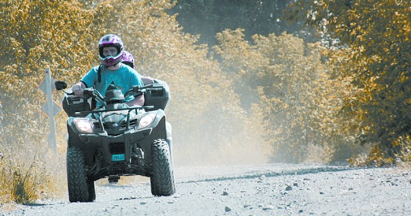 Sharing the same machine, two young ATVers ride through Washburn on a multi-purpose recreational trail. More than 1,200 miles of trails connect Aroostook County destinations.