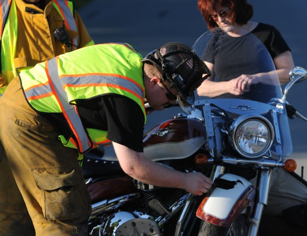 A Hermon firefighter inspects the damage to a 2008 Suzuki driven by David McCarty of Hermon after he collided with a car driven by Vicki Gonyea, also of Hermon, on Route 2 in Hermon on Monday, June 18, 2012.