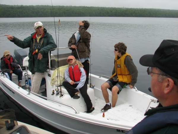 Stuart Langton of Sanibel, Fla., (in white hat) and his family chat with Joseph McBrine and Wayde Carter (off camera) of the Maine Warden Service on Saturday, June 23, 2012, on Hadley Lake in East Machias. Carter and McBrine were conducting boat safety checks as part of the service's Operation Dry Water program.