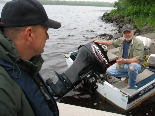 Maine Game Warden Wayde Carter (left) chats with Scott Verburgt on Saturday, June 23, 2012 on Hadley Lake in East Machias. Carter and fellow Warden Joseph McBrine were conducting boat safety checks on lakes in the Machias area Saturday as part of the warden service's Operation Dry Water.