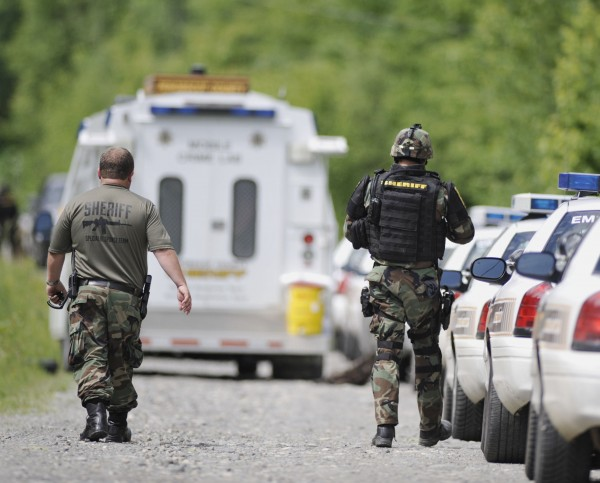 A Penobscot County Sheriffs Department tactical team deploys on Brimstone Road, LaGrange, Maine, during a possible hostage situation Thursday, June 28, 2012.