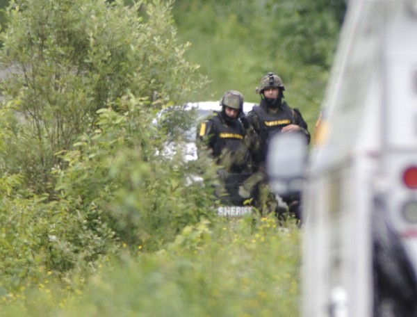 A Penobscot County Sheriffs Department tactical team waits at the end of a driveway on Brimstone Road, LaGrange, Maine, Thursday, June 28, 2012, during a possible hostage situation.