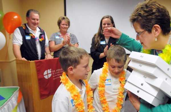 St. Joseph Healthcare CEO Mary Prybylo (right) hugs twin brothers John (second from right) and Joshua Fitzpatrick after the boys handed her five iPads as a donation. The boys' mother Kim Fitzpatrick (second from left) works at and was also treated for cancer at the St. Joseph Healthcare Infusion Therapy Center. Kim's husband, Andy (left), wrote a book about the family's experience and they used the proceeds to purchase the iPads for the Infusion Therapy Center.