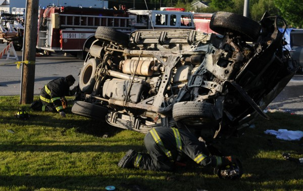 Bangor firefighters look under a vehicle that was involved in a three-vehicle fatal accident in front of Gifford's Ice Cream on Broadway in Bangor on Sunday, June 10, 2012.