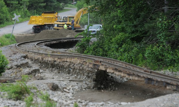 Construction workers repair a secion of railroad track in Brownville on Monday, June 25, 2012, that was washed out by flash flood waters on Sunday.