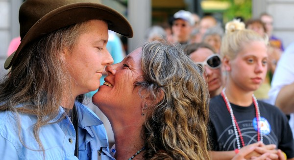 Lynn Audet (left) and Gretchen Cates of Moscow kiss during a commitment ceremony during the Pride Festival at West Market Square in Bangor Saturday.  They have been partners for a year and this is the first Pride Festival they attended.