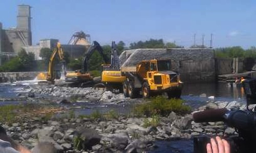Crews start to hammer away at the Great Works dam on Monday morning.