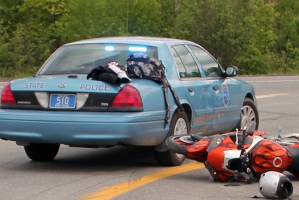 An orange 2002 Yamaha motorcycle lies near a state police cruiser it hit in the northbound off-ramp of Interstate 95 in Howland after a high-speed chase that began in Orono on Thursday, June 7, 2012.