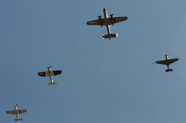 Four World War II-era airplanes fly over the Bangor International Airport, honoring the last reunion of World War II's 5th Armored DIvision Sunday. The aircraft participating in the flyover were from left: P-51 Mustang, F-4 Corsair, B-25 Mitchell and a P-40.  The aircraft belong to the Texas-based Flying Legends Museum.