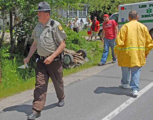 Penobscot County Sheriff's Deputy Peter Stone gathers information on an accident in which an elderly man was injured when the man's sedan went off Lee Road into a ditch near Dubay's Bait shop in Lee on Sunday, June 17, 2012.