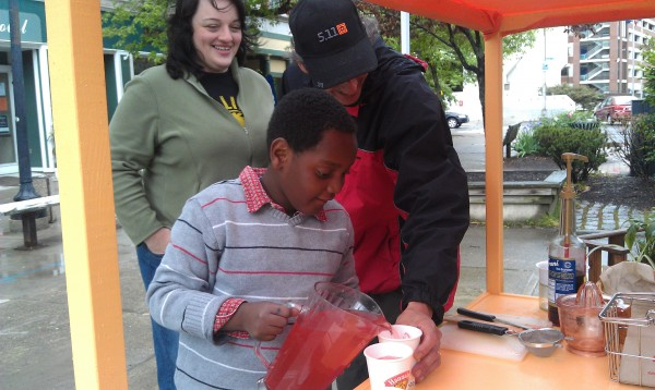 Isaac Renshaw-Sirimoglu, 7, pours a glass of lemonade for a customer at his lemonade stand in West Market Square in downtown Bangor on Sunday afternoon. Isaac is attempting to raise $1,500 so his parents can start the process of adopting a little brother for him. Isaac was adopted from Haiti as a 14-month-old. His parents, Jodi Renshaw and Halise Sirimoglu helped him in his fundraising efforts throughout the day.