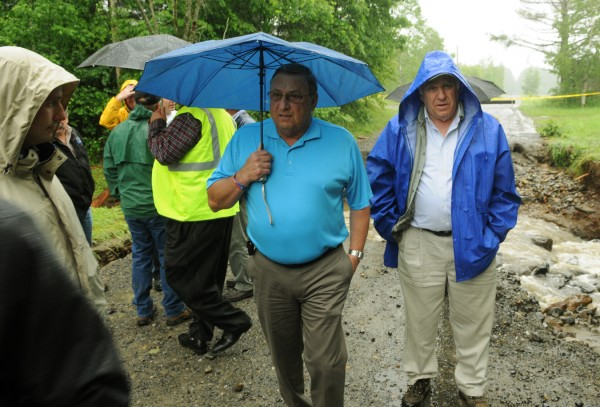 Maine Gov. Paul LePage and state Rep. Paul T. Davis Sr. inspect the washed out road on Pleasant River Road in Brownville on Tuesday, June 26, 2012. One person died at the site when rain waters caused the road to give way leaving leaving a crevice which the victim drove in to. LePage was in town to see the devastation first hand.