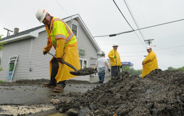 A Maine DOT worker shovels up loose gravel along Main Street in Brownville on Tuesday, June 26, 2012. Severe fooding in the region prompted Maine Gov. Paul LePage to vist the area to see the devastation for himself.