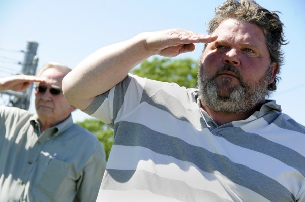 Terry White of Hermon (right) and another area resident pay their respects with a military salute as Capt. John &quotJay&quot Brainard III's casket is delivered from a transport plane to a hearse which had a motorcade escort to Newport Thursday morning, June 14, 2012.