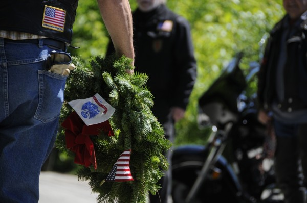A Patriot Guard Rider holds a memorial tribute wreath while gathered with other supporters, friends and family of Army pilot Capt. John &quotJay&quot Brainard III after his casket arrived by motorcade in Newport on Thursday, June 14, 2012.