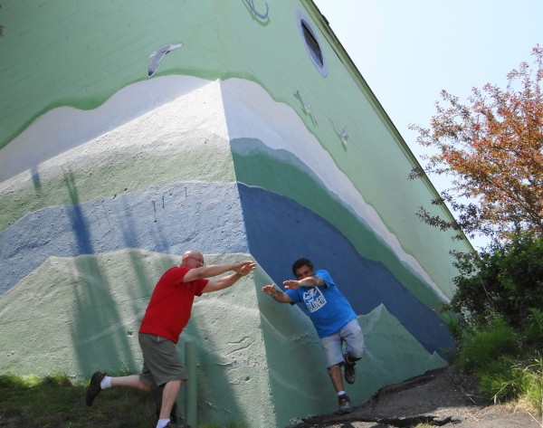 Artists David Hurley (left) and Russell Kahn pretend to swim the waves that come off the hull of the SS Belfast. The men painted the side of the Family Dollar Store to resemble a ship.