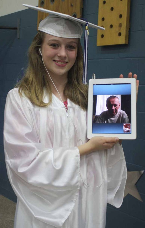 Recent  Woodland Consolidated School eighth-grade graduate Adrianna Bither poses with her father, Steve Bither, following the graduation ceremony on June 6. Though Steve is currently at a cancer clinic in Mesa, Arizona, he was able to attend the Woodland graduation ceremony through real-time video chat on a tablet computer.