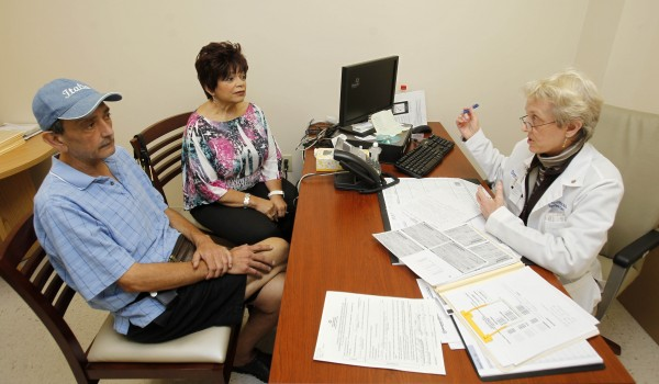 In this photo taken Wednesday, May 16, 2012,  Dr. Pamela Sutton, right, talks to patient Carol Delzatto, center, and her husband Paul Delzatto at Broward General Hospital in Fort Lauderdale, Fla. Hospitals across the country have been adding programs in palliative care, which focus is on treating pain, minimizing side effects, coordinating care among doctors and ensuring the concerns of patients and their families are addressed.