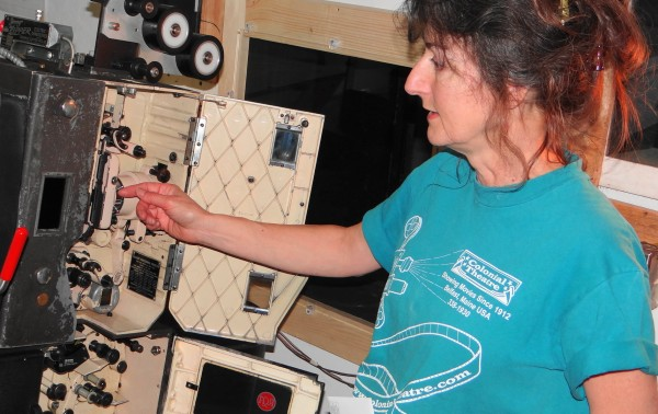 Therese Bagnardi, co-owner of the Colonial Theatre in Belfast, points to the insides of one of the 35-millimeter film projectors being replaced by digital equipment.