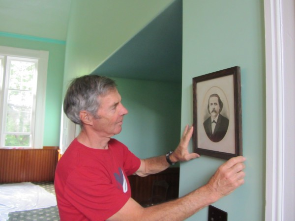 Roy Bennett shows a portrait of the church's first minister, the Rev. Jason Marriner, in the Rockville Community Chapel.