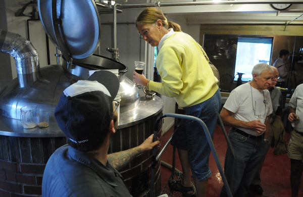 Linda Blicker of Hancock, New Hampshire peers into the brew pot at the Sea Dog Brewing Company in Bangor on Wednesday, June 27, 2012 while sipping a Sea Dog draft and listening to brew master Brooks Mathews (left) during a tour at the grand opening of the new barrel room.