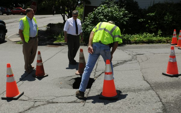 City of Bangor officials from the department of engineering and public works inspect a shallow sinkhole that opened up on Middle Street on Thursday, June 28, 2012. It was determined that recent rains coupled with a collapsed sewer line caused the sinkhole.