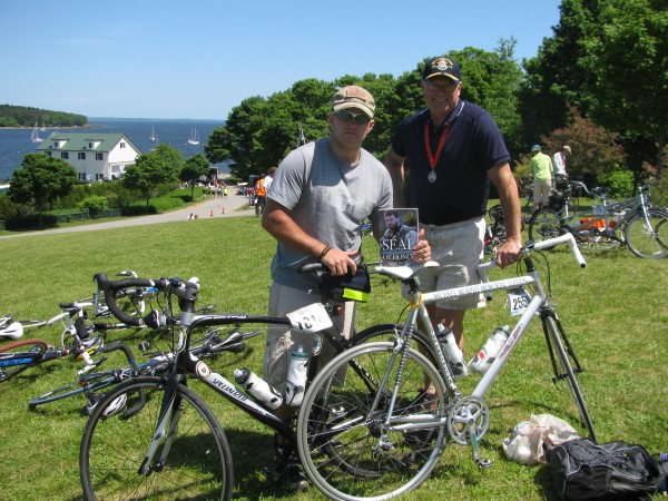 Trek Across Maine finishers Parker Christensen (left) of Brunswick and Terry Smith of Topsham pose with their bikes and a book which tells the story of Michael Murphy, their inspiration. Murphy was a Navy Seal who died in a firefight in Afghanistan in 2005. &quotI believe it was the spirit of Michael Murphy pushing me,&quot Christensen said of his experience with the 180-mile bike journey.