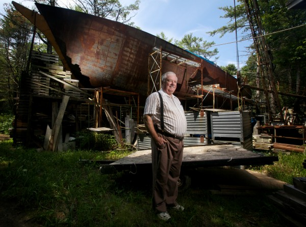 Harold Arndt stands in front of his 113-foot-long, unfinished, steel schooner made completely out of reclaimed materials in a residential Freeport neighborhood in July. Arndt has been working on the boat for almost 20 years.