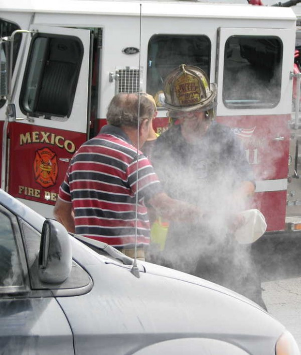 Deputy Chief Richie Jones of the Mexico Fire Department brushes a sodium bicarbonate-based fire suppressant off Silas Sherry of Andover on Friday at the Mexico Food Trend/Circle K.