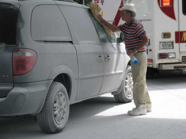 Silas Sherry of Andover wipes white dust off his Dodge Grand Caravan Sport minivan Friday while covered with a sodium bicarbonate-based fire-extinguishing agent.